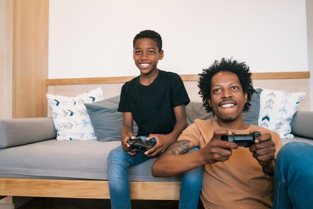 Vader en zoon spelen thuis samen videospelletjes. Gratis Foto