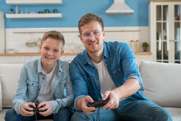 Vader en zoon spelen van videogames met controllers Gratis Foto