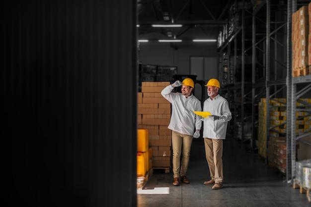 Vader en zoon staan in hun magazijn met helmen op hun hoofd en kijken naar pakket voorbereid voor transport. er trots en tevreden uitzien. Premium Foto