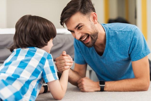 Vader en zoon strijden in armworstelen en liggen op de grond Premium Foto