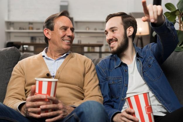 Vader en zoon tv kijken in de woonkamer Gratis Foto