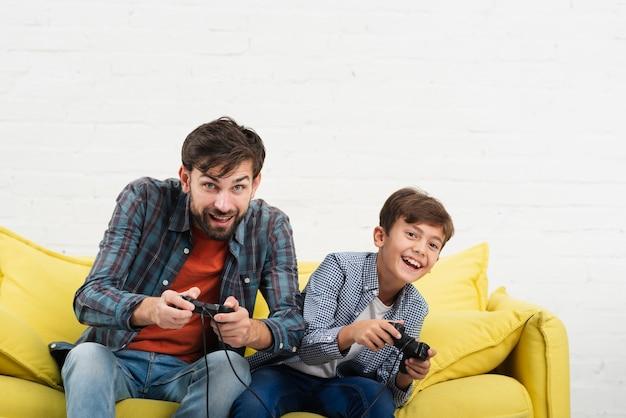 Vader en zoon zittend op een bank en spelen op console Gratis Foto