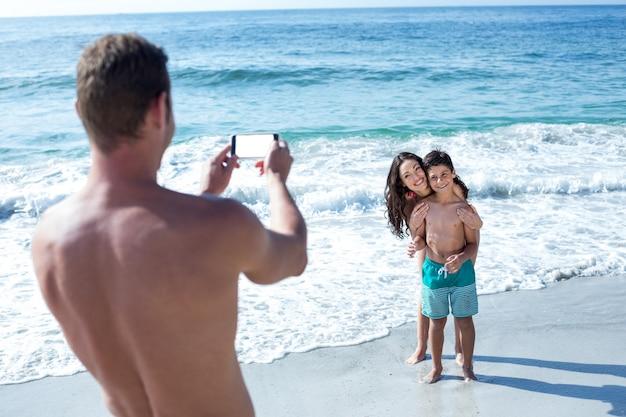 Vader fotografeert gelukkige vrouw en zoon Premium Foto