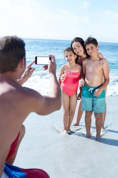 Vader fotografeert kinderen en vrouw op zee Premium Foto