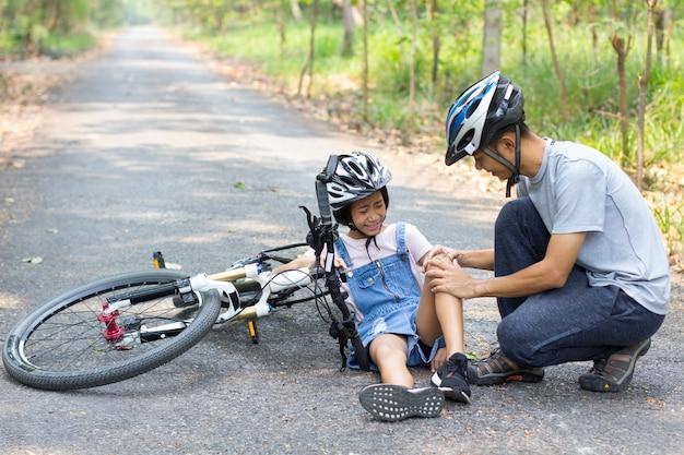 Vader heeft de dochter geholpen om van de fiets te vallen. fietsen op straat. Premium Foto