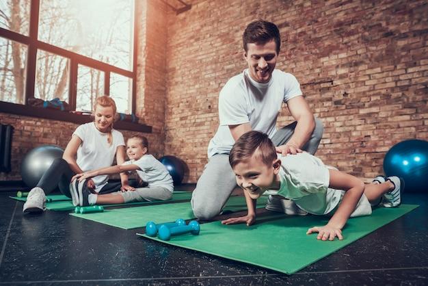 Vader helpt zoon met push-ups. moeder stretch dochter. Premium Foto