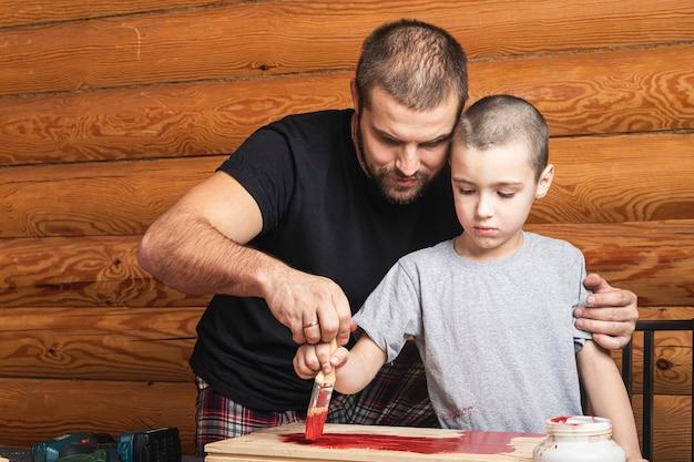 Vader houdt een penseel met rode verf in zijn hand en schildert een houten oppervlak, leert zijn zoon schilderen Premium Foto