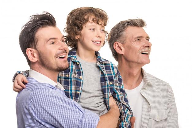 Vader houdt zijn zoon in zijn armen, grootvader is dichtbij. Premium Foto
