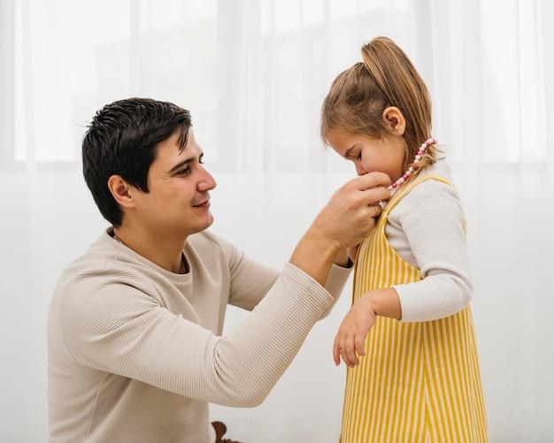 Vader krijgt zijn dochter thuis gekleed Gratis Foto