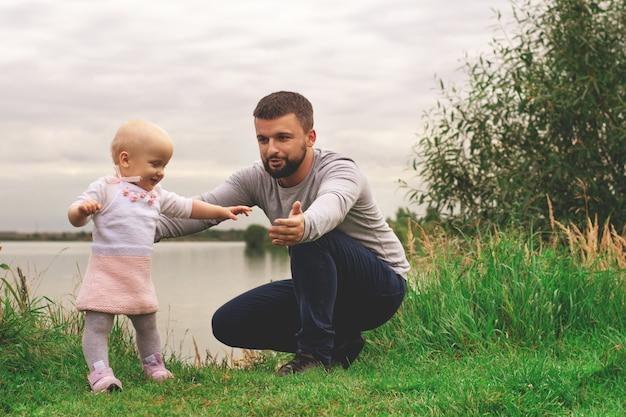 Vader leert dochter om te wandelen, te parkeren, de natuur. lopen op het gras. vader en dochter. eerste stappen. Premium Foto