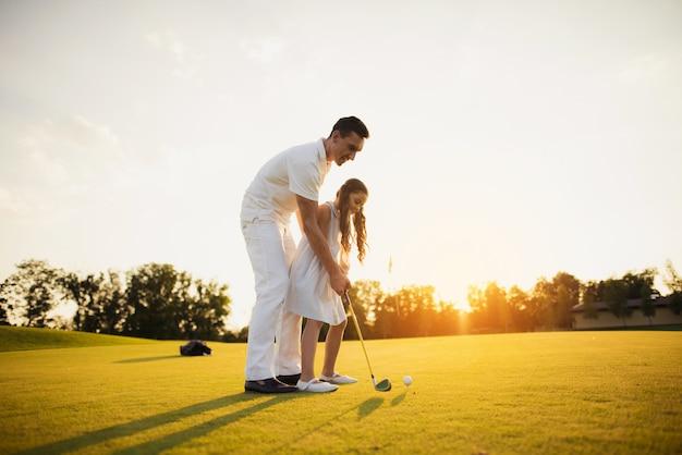 Vader leert kind om golfgeschoten familiehobby te nemen. Premium Foto