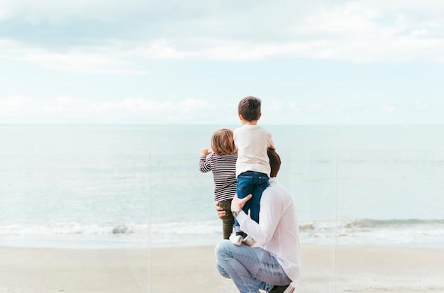 Vader met jongens die op zee kijken Gratis Foto