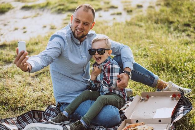 Vader met zijn zoon die picknick in het park heeft Gratis Foto