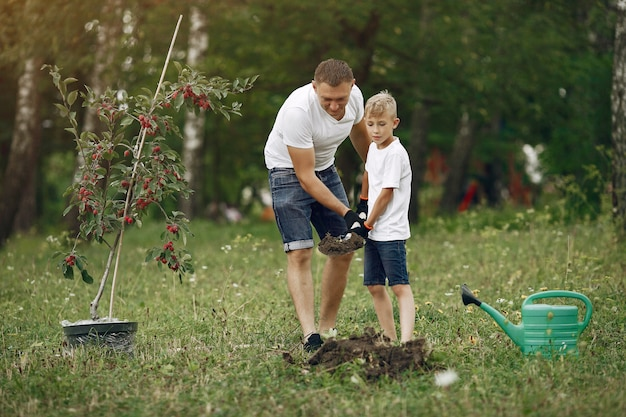 Vader met zoontje plant een boom op een erf Gratis Foto
