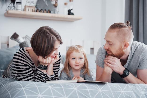 Vader, moeder en dochtertje lezen kinderboek op een bank in de woonkamer. gelukkige grote familie las een interessant boek op een feestelijke dag. ouders houden van hun kinderen Premium Foto