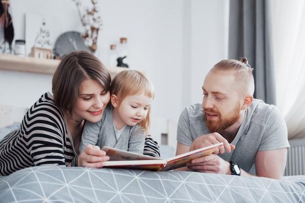 Vader, moeder en dochtertje lezen kinderboek op een sofa in de woonkamer. gelukkige grote familie las een interessant boek op een feestelijke dag. ouders houden van hun kinderen Premium Foto
