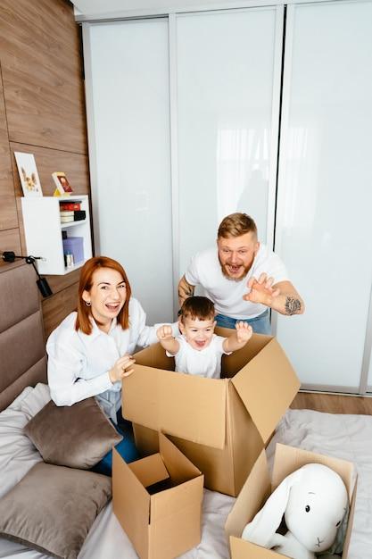 Vader, moeder en zoontje spelen in de slaapkamer met papieren dozen Gratis Foto