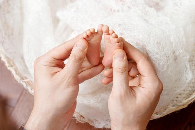 Vader of arts die de voet van kleine baby masseren. vader zachtjes benen van een pasgeboren kind in handen houden. gelukkig gezin . Premium Foto