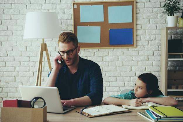 Vader praat aan de telefoon en het meisje neemt aanstoot aan hem. Premium Foto