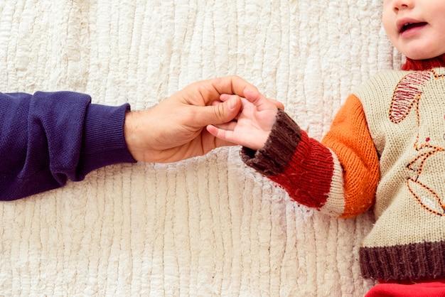 Vader schudt handen met zijn babydochter liggend in bed. Premium Foto
