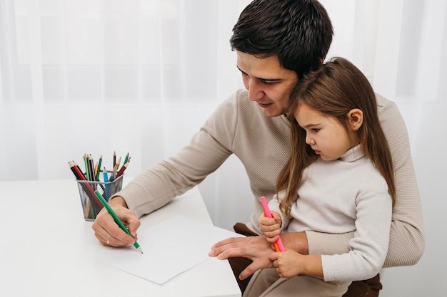 Vader speelt met kleurpotloden met dochter Gratis Foto