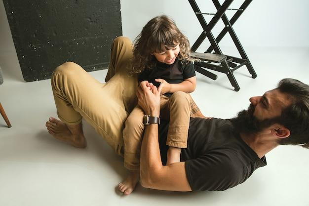 Vader spelen met jonge zoon in hun zitkamer thuis. jonge vader die plezier heeft met zijn kinderen in vakanties of weekend Gratis Foto