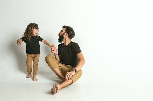 Vader spelen met jonge zoon. jonge vader plezier met zijn kinderen in vakanties of weekend. concept van ouderschap, kinderjaren, vaderdag en familierelatie. Gratis Foto