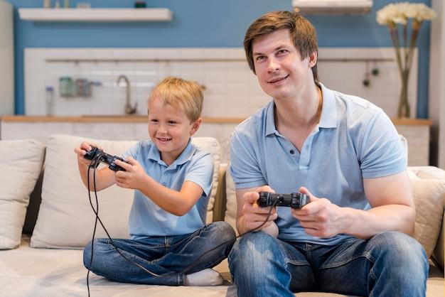 Vader spelen van videogames samen met zoon Gratis Foto