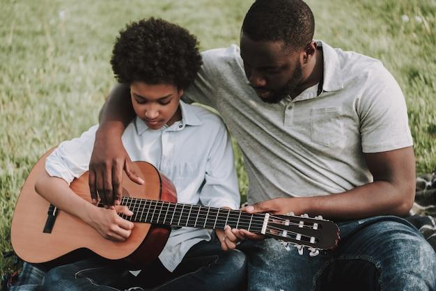 Vader toont lessen om te spelen op gitaar van zoon Premium Foto