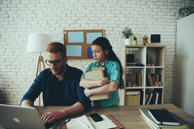 Vader werkt op de computer en een boos meisje staat in de buurt. Premium Foto