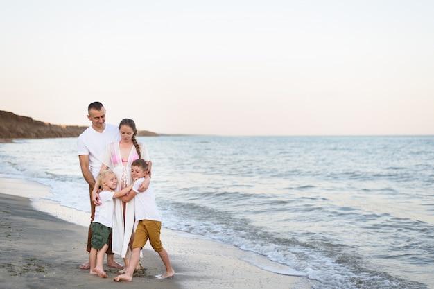 Vader, zwangere moeder en twee zonen aan de zeekust Premium Foto