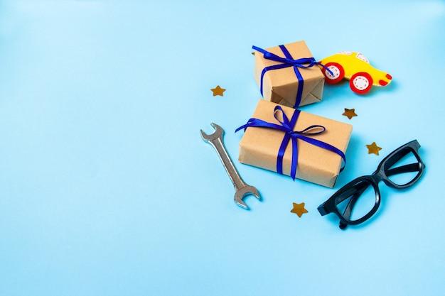 Vaderdag concept kaart met man's werk hulpmiddel op blauwe achtergrond en geschenken vakken verpakt in kraftpapier Premium Foto