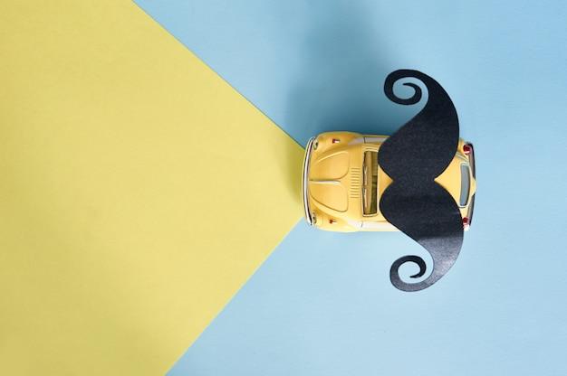 Vaderdag wenskaart met gele speelgoedauto en zwart papier snor Premium Foto