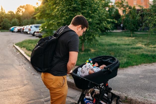 Vaderpapa met pasgeboren kinderwagenwandelwagen buiten tijdens de zonsondergang van de de zomeravond Premium Foto