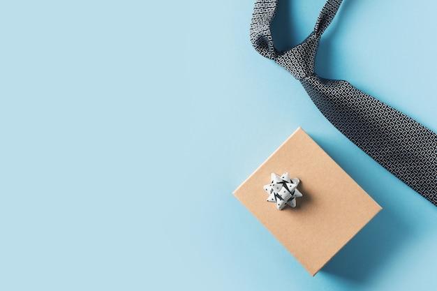 Vaders dag concept met geschenkdoos en stropdas op blauwe achtergrond Premium Foto