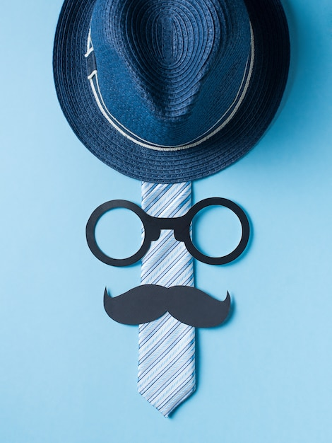 Vaders dag concept met hoed, bril en stropdas op blauwe achtergrond Premium Foto