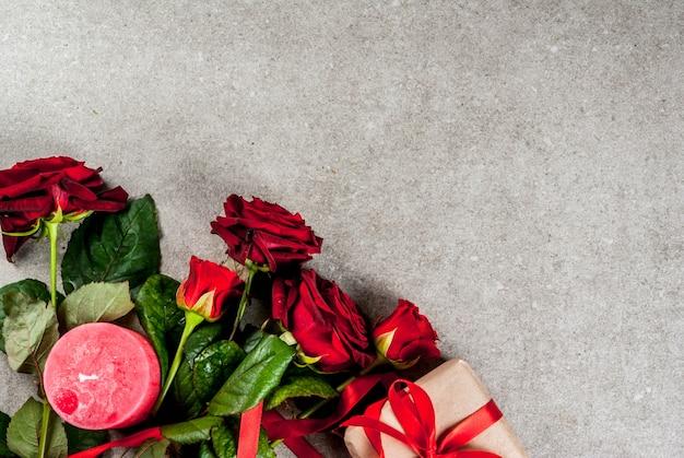 Vakantie achtergrond, valentijnsdag. boeket van rode rozen, stropdas met een rood lint, met verpakte geschenkdoos en rode kaars. kopieer op een grijze stenen tafel het bovenaanzicht van de ruimte Premium Foto