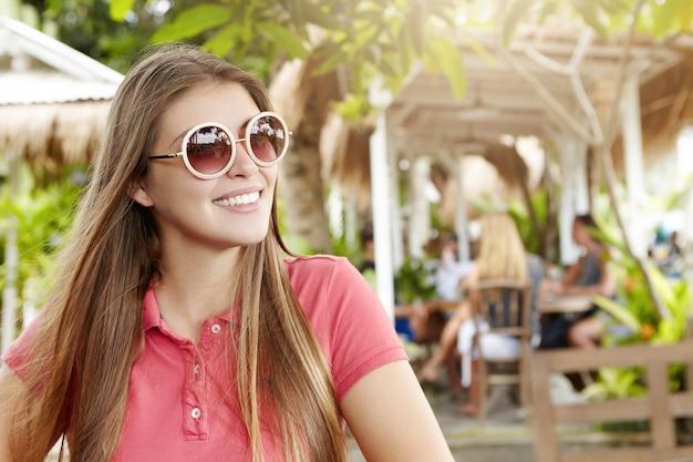 Vakantie concept. buiten schot van mooi meisje in trendy tinten en poloshirt glimlachend vreugdevol terwijl u ontspant in café in kuuroord, vakantie doorbrengen in hete exotische land. Gratis Foto