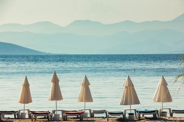 Vakantie concept, witte parasols, blauwe zee en grote bergen op horizon Premium Foto