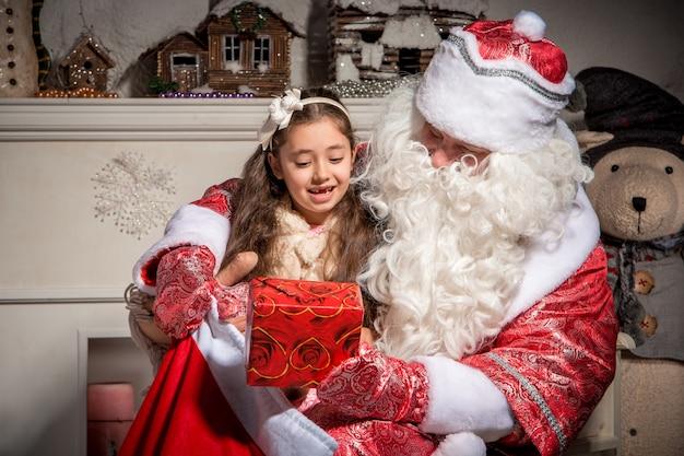 Vakantie en mensenconcept - glimlachend meisje met de kerstman Gratis Foto