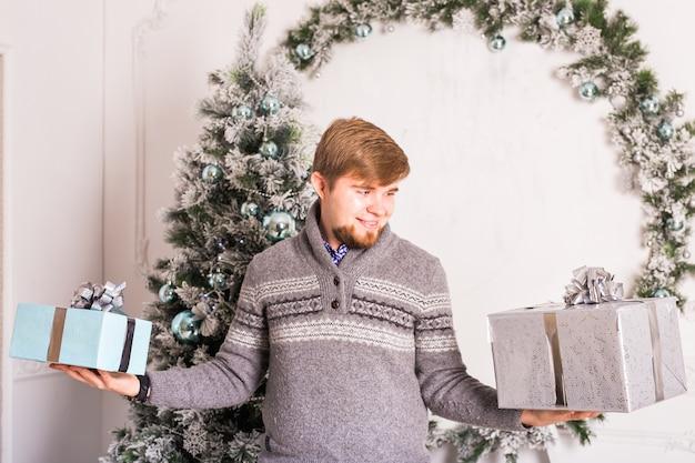 Vakantie en speciale gelegenheid. man die geschenkdoos geeft. man verstopt aanwezig. verrassing. Premium Foto