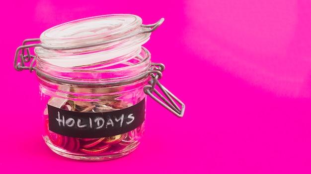 Vakantie glazen pot met munten en eurobiljetten op roze achtergrond Gratis Foto