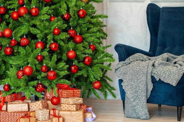 Vakantie interieur. mooi versierde kerstboom met blauwe fauteuil Premium Foto