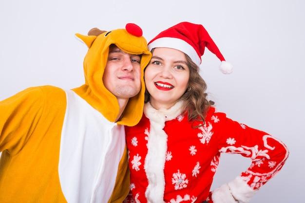 Vakantie, kerstmis en leuk concept - grappig paar in herten en kerstmankostuum die elkaar op witte muur koesteren. Premium Foto