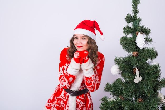 Vakantie, kerstmis en leuk concept - grappige vrouw in santa claus-kostuum dichtbij kerstboom op witte muur. Premium Foto