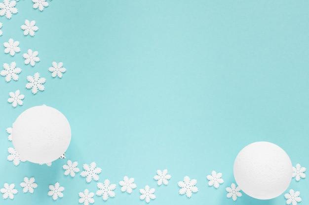 Vakantie pastel achtergrond, witte sneeuwvlokken en kerstbal op een zachte blauwe achtergrond, plat lag, bovenaanzicht Premium Foto