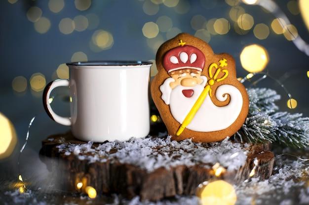 Vakantie traditionele gerechten bakkerij, gingerbread oude vriendelijk tovenaar in gezellige inrichting met slinger lichten en een kop warme koffie Premium Foto