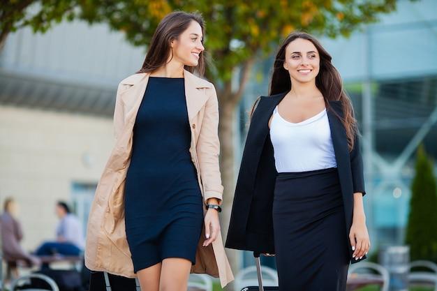 Vakantie, twee gelukkige meisjes die samen naar het buitenland reizen, kofferbagage op de luchthaven dragen Premium Foto