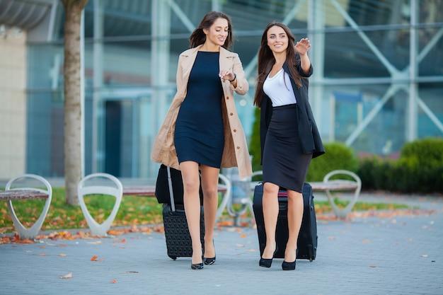 Vakantie. twee stijlvolle vrouwelijke reizigers lopen met hun bagage in de luchthaven Premium Foto
