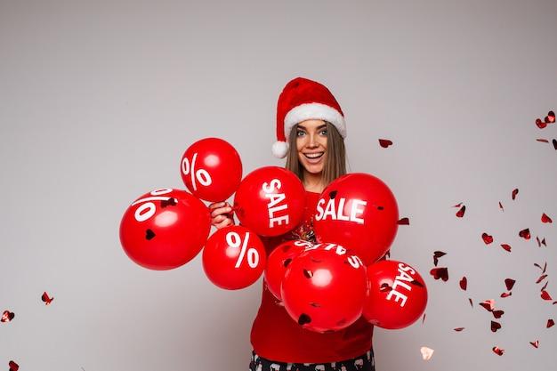 Vakantie verkoop en korting, mooi meisje in een rode hoed met ballonnen op grijs Premium Foto